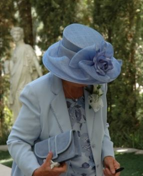 wedding guest in hat arriving at the church