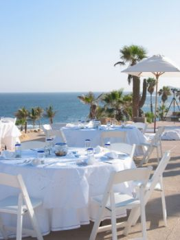 The tables are laid for a beautiful beach side reception